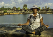 Woman relaxing with Angkor Wat having saved for bucket list ideas