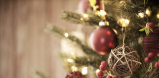 Live Christmas Tree with Eco Friendly Decorations, Ornaments and Gifts on an Old Wood Background