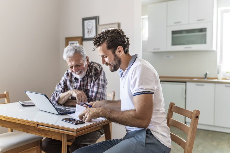 Senior and younger man discuss what age to start saving for a pension