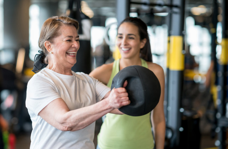Adult woman exercising at the gym with a personal trainer and looking very happy