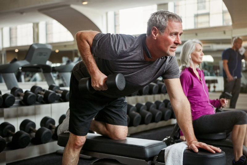 Weight lifting for seniors working out together at the gym