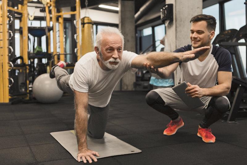 Senior man doing balance exercise with trainer