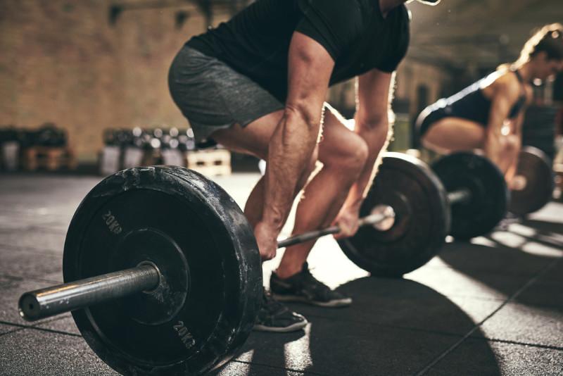 Backache prevention exercise carefully strong man doing deadlift training in gym