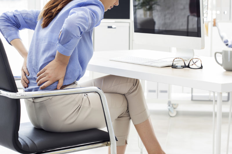 Backache prevention A generic photo of a woman experiencing back pain at work.