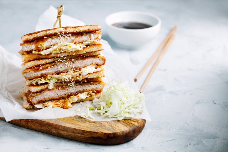 Food trends 2020 Katsu Sando - traditional Japanese cutlet sandwich with deep fried pork,cabbage,Japanese mayonnaise and ton katsu sauce on a light background close-up with copy space for text. Japanese fast food