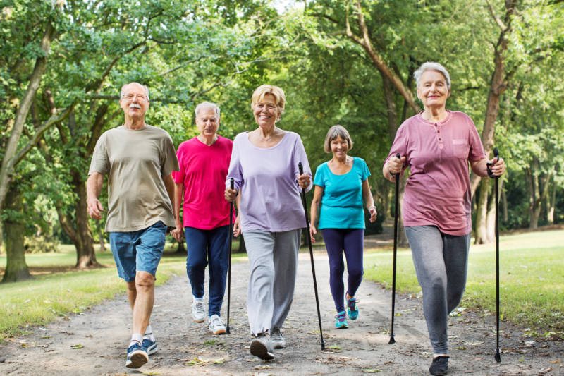 Joint pain drug-free relief Group of active seniors walking on road through park in morning