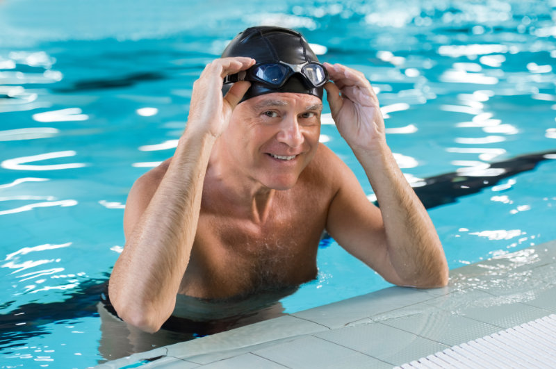 Joint pain drug-free pain relief Smiling man in a swimming pool wearing swim cap and goggles on his head. Portrait of a satisfied senior man after swimming in the pool. Retired proud man leaning at the poolside looking at camera.