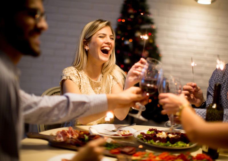Christmas wellbeing tips Group of young people celebrating New Year and drinking red wine