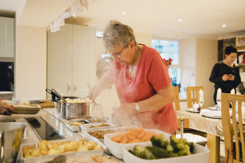 Wellbeing Christmas tips Senior woman standing in the kitchen while preparing Christmas dinner.