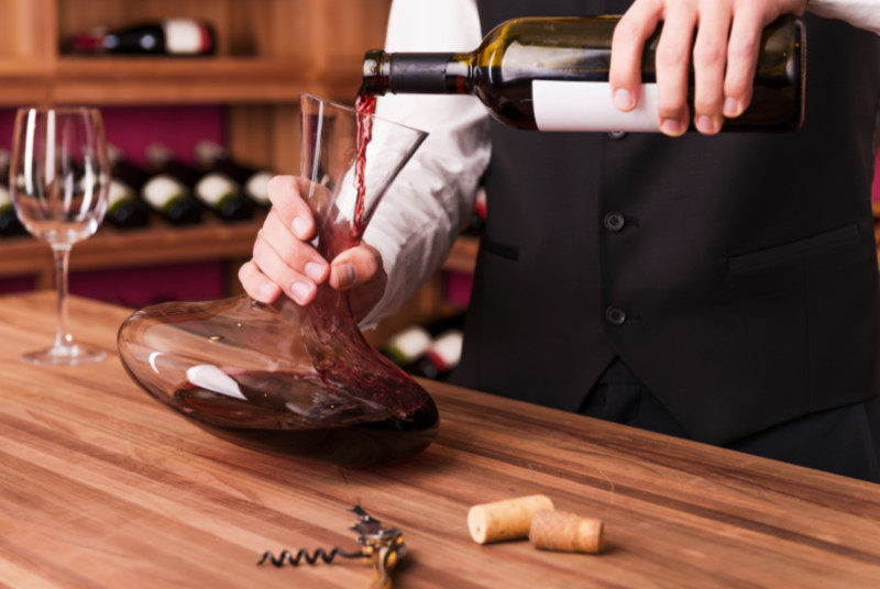 Wine serving tips Confident male sommelier pouring wine to decanter while standing near the wine shelf