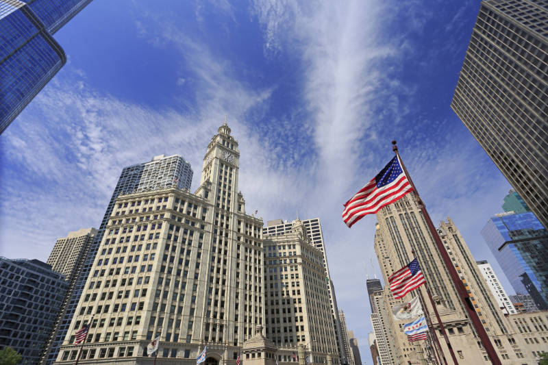 Wrigley Building and Tribune Tower on Michigan Avenue with Illinois flag on the foreground in Chicago