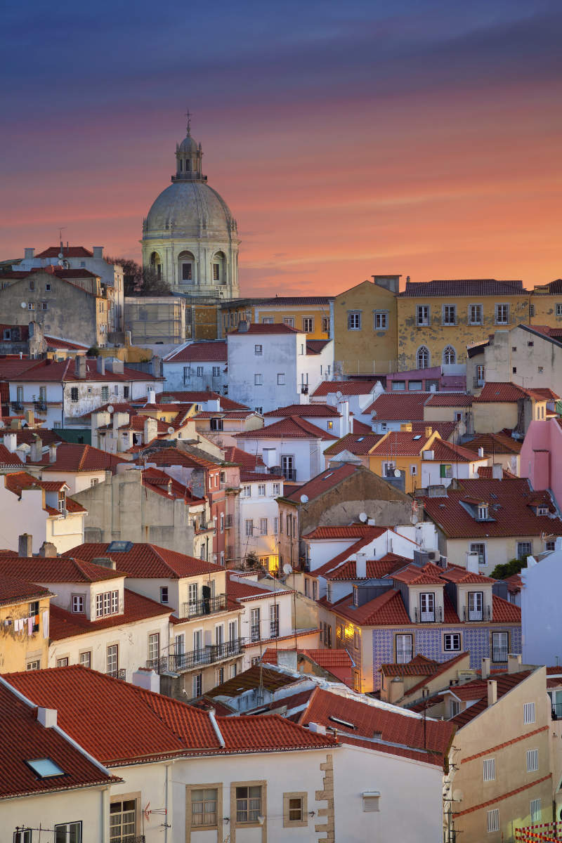 best European cities to visit in winter Image of Lisbon, Portugal during dramatic sunrise.