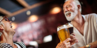 How to cure a hangover quickly senior couple in a pub drinking beer and wine.