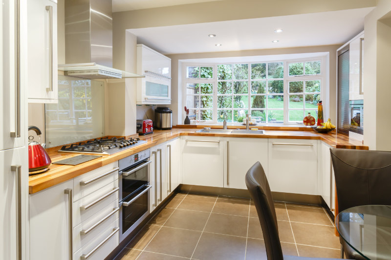 Add value to your home with a new kitchen Modular modern kitchen interior with white units and contemporary dining area