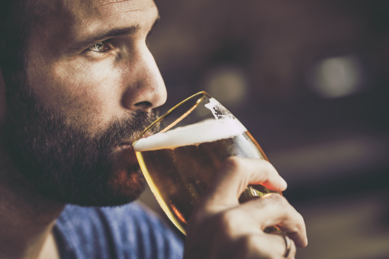 Close up of mid adult man drinking beer in a bar and lookåing away.