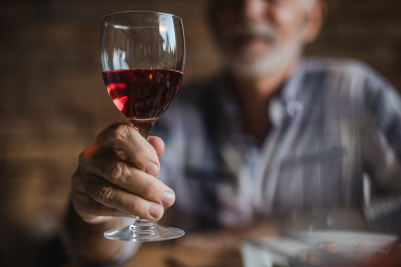Close up of unrecognizable mature man holding wineglass.