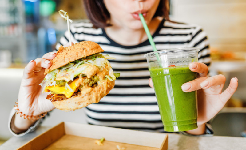 Flexi-veganism A young woman drinks green smoothies and eats a burger in a vegan fast food restaurant