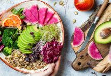 Flexi-veganism Girl holding vegan, detox Buddha bowl with quinoa, micro greens, avocado, blood orange, broccoli, watermelon radish, alfalfa seed sprouts.