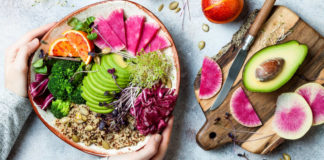 Flexi-veganism Girl holding vegan, detox Buddha bowl with quinoa, micro greens, avocado, blood orange, broccoli, watermelon radish, alfalfa seed sprouts.