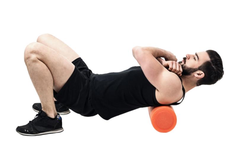 Foam roller back exercises Athlete massaging upper back muscles with foam roller. Full body length portrait isolated on white studio background.