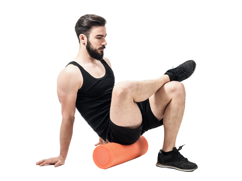 Foam roller back exercises Athlete massaging glutes muscles with foam roller. Full body length portrait isolated on white studio background.