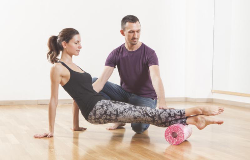 Foam roller back exercises Pilates instructor coaching a beautiful woman using foam roller