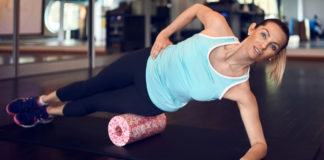 Foam roller back exercises Woman in mint sleeveless shirt and black leggings in gym doing exercise with foam or fascia roll and looking at camera.