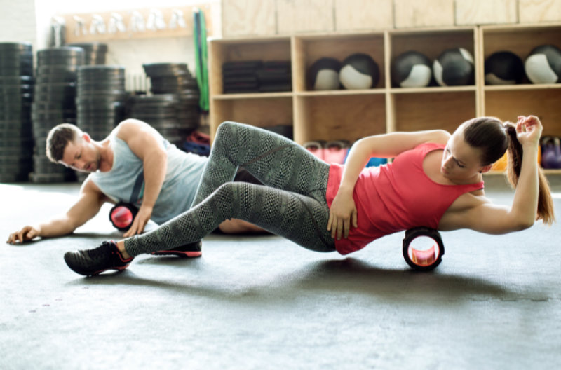Foam roller back exercises Young man and woman doing pilates on support roller at modern gym