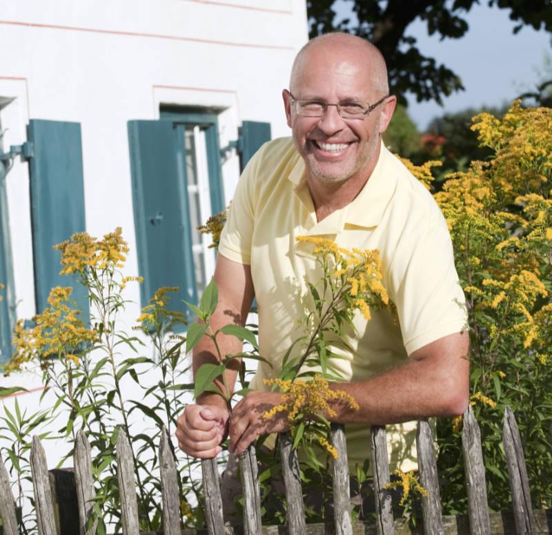 Germany, Bavaria, Senior man leaning against garden fence, smiling, portrait