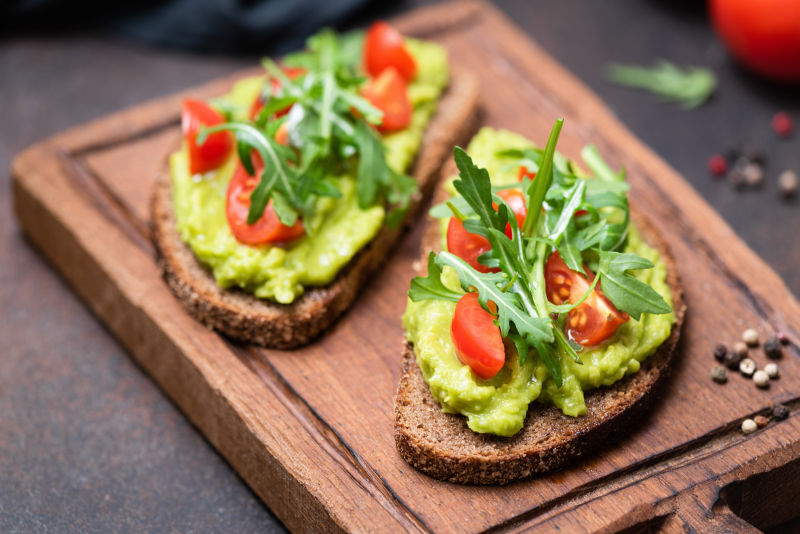 Rye bread health benefits Healthy vegan toast with avocado, tomato, arugula on wooden serving board, closeup view, horizontal image. Snack, lunch or vegan breakfast