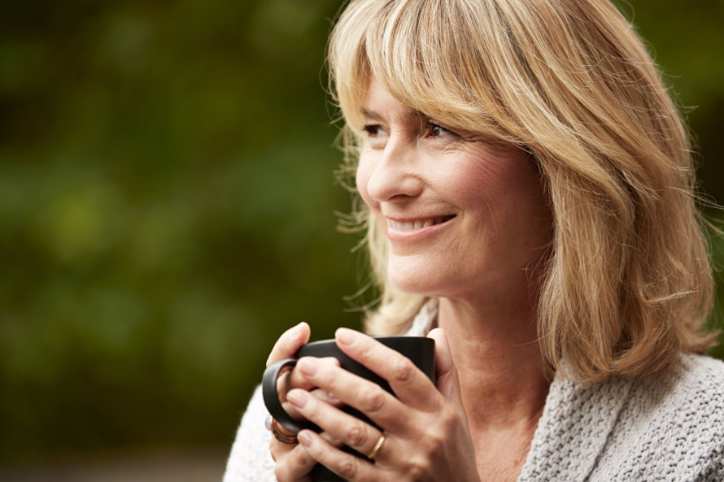 Health benefits of tea Shot of a mature woman standing in her yard drinking a cup of tea