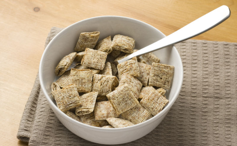 High fibre foods A close-up of a bowl of bite-size shredded wheat on a wooden surface.