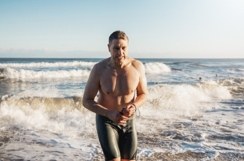 Mental health benefits of swimming A muscular mature man can be seen emerging from the north sea on an early morning, he is wearing black swimwear.