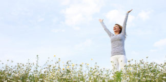 Non-HRT menopause treatment Woman with stretched arms in flower field