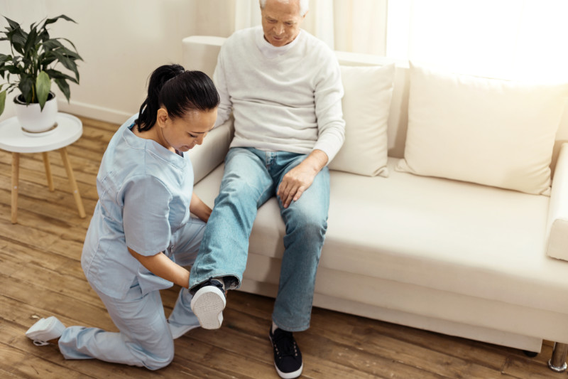 Special exercise. Pleasant professional experienced caregiver sitting on one knee and warming up her patients leg while doing special psychical exercises