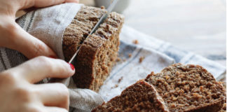 Health benefits of rye bread The girl cuts whole-wheat rye bread on a wooden table.