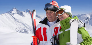 Skiing is good for you Smiling senior couple on winter ski vacation by mountains