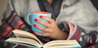 woman reading a book and holding a mug of hot beverage