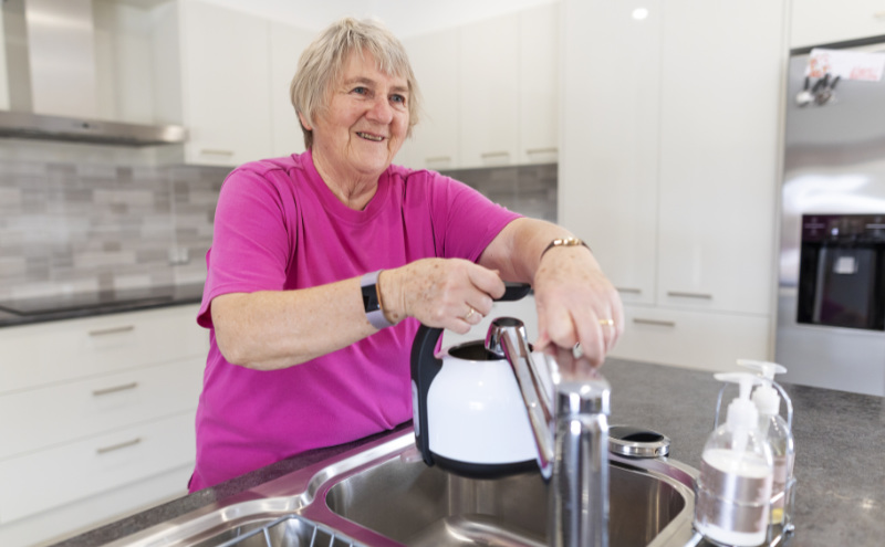 Water saving tips Senior woman filling a kettle with water to make a cup of tea or coffee