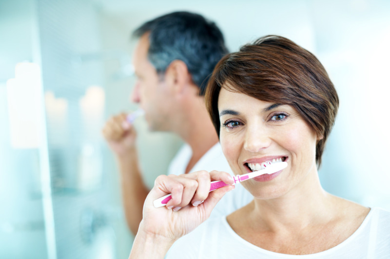 Water saving tips Smiling mature woman brushing her teeth with her partner behind her - portrait