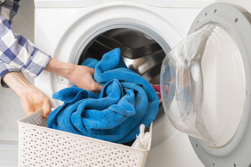 Water saving tips persons hand put dirty clothes in the washing machine