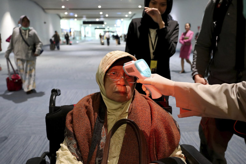 A traveller gets their body temperature checked when arriving into Indonesia (Tatan Syuflana/AP)