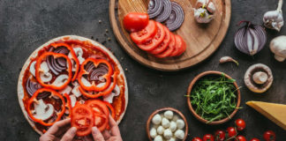 Cut calories cropped shot of woman spreading bell pepper slices onto pizza on concrete table