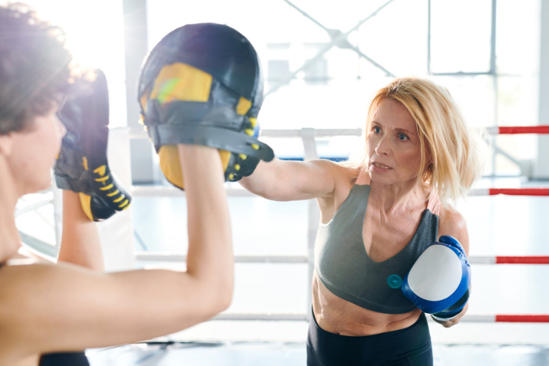 Gym confidence Blonde aggressive sportswoman hitting her young rival with boxing glove while preparing for competition