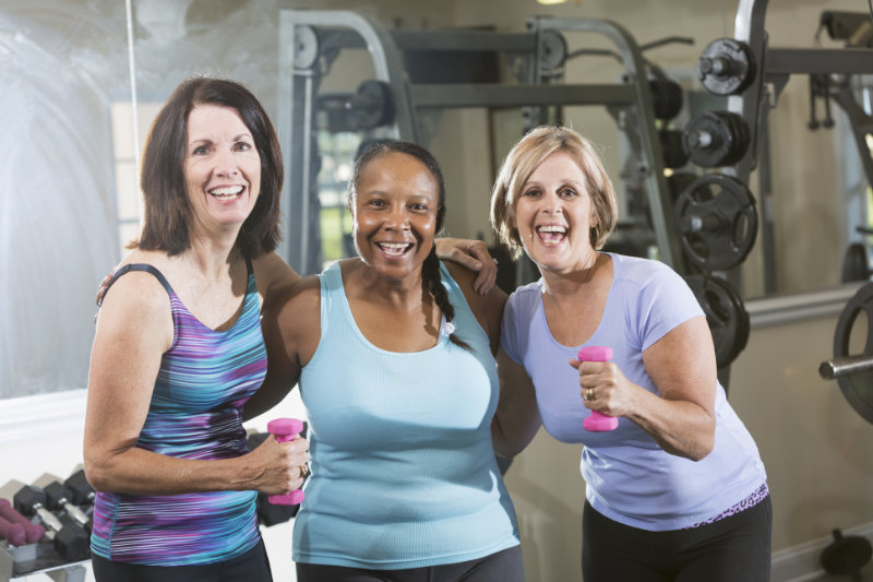 Gym confidence Multi-ethnic group of mature women (50s) exercising in gym, lifting hand weights.
