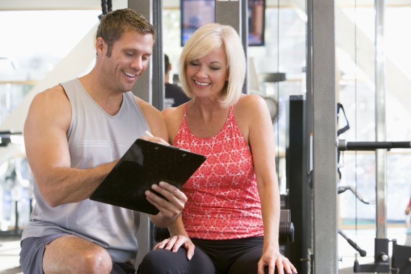 Gym confidence Personal Trainer talking through induction with woman
