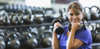 Gym confidence Middle aged Hispanic woman at a gym working out, lifting hand weights. She has a dumbbell in each hand, strengthening her arms and biceps. She is smiling at the camera.