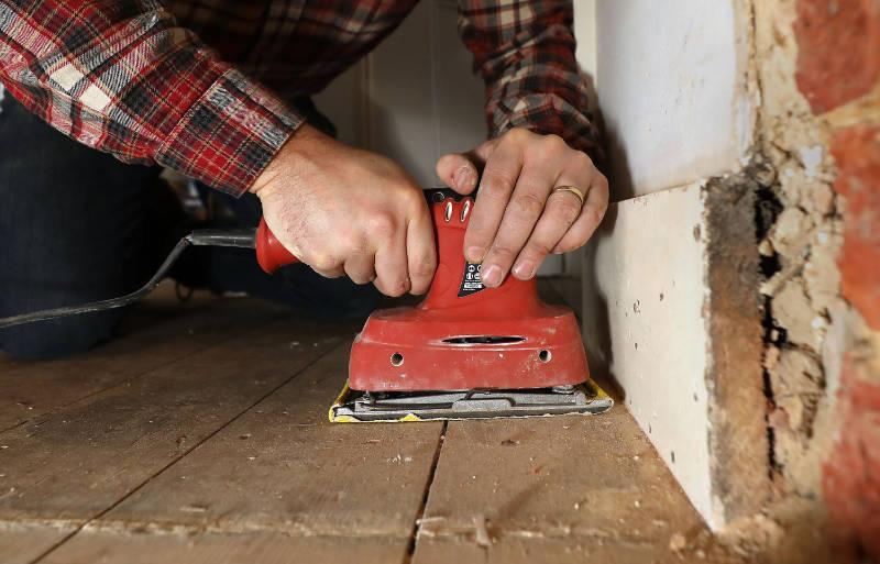 Richard Burr sands the corners of a floor (Philip Toscano/PA).
