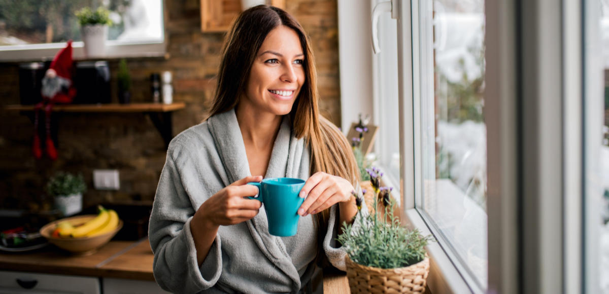 Slow living woman looking out of a window holding coffee cup