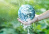 Save water save money Water pouring on planet earth placed on human hand for saving resources and heal the world campaign, environment issues, Elements of this image furnished by NASA.